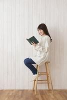 椅子に座って本を読む日本人女性