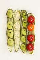 空豆のさやに納まる空豆と米とミニトマトで作った人の顔