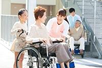介護士と孫と車いすに乗った中高年女性