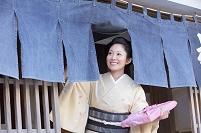 暖簾をくぐる着物の女性