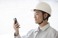 スマートフォンを見る男性作業員