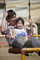 ブランコで遊ぶ娘と父親