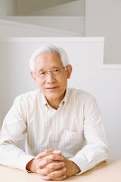 手を組むシニアの日本人男性