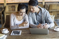 カフェでスマートフォンを操作しているカップル