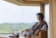 客室でくつろぐシニアの日本人男性