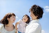 公園で娘を抱く両親