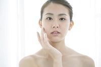 頬に手をあてるナチュラルメイクの20代日本人女性
