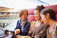 雑誌を見つめる日本人女性3人組