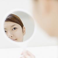 手鏡に映る日本人女性の顔