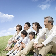 草原に座る日本人の三世代家族