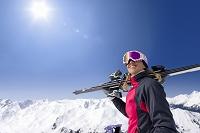 スキー板を担いだ笑顔の女性