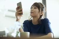 部屋でスマホを見る日本人女性