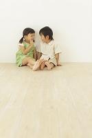 フローリングの部屋に座る男の子と女の子