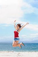 海辺で手を挙げてジャンプする日本人女性