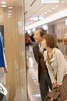 ウインドーショッピングをする中高年夫婦