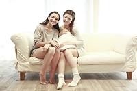 ソファに座って微笑む若い女性