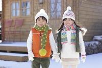 雪景色の中で手を繋ぐ男の子と女の子