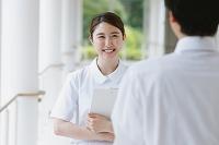 廊下で会話する笑顔の若い日本人女性看護師