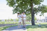 住宅街の新緑と笑顔の日本人家族