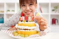 ケーキにろうそくを挿す女性