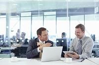 ノートPCとタブレットを使うビジネスマンたち