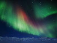 スウェーデン 雪山の上の赤と緑のオーロラ