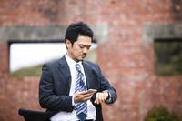 腕時計を見る日本人ビジネスマン