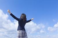 青空と伸びをする女子高校生