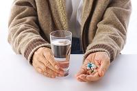 薬と水を持っているシニア