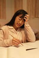 深夜の勉強中に頭痛に苦しむ女の子