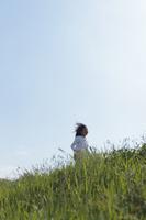 風に吹かれながら草原を走る女の子