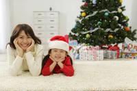 クリスマスツリーの前でうつ伏せになる日本人親子