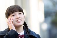 電話で話をする女子高校生
