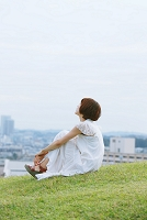 芝生の上で考え事をする女性