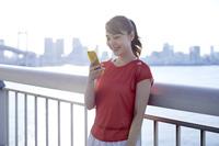 スマートフォンを見るランニングウェア姿の日本人女性