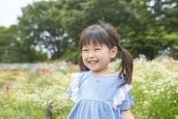 花畑の前に立つ日本人の女の子