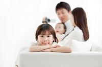 ソファに座る日本人家族とビデオカメラ