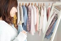 鏡の前で洋服を選ぶ日本人女性