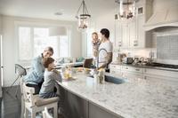 キッチンで朝食をとる外国人家族