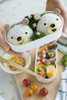 クマのキャラクター弁当を持つ女性