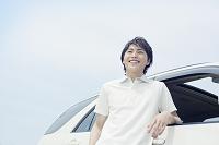 車に寄りかかる笑顔の若い男性