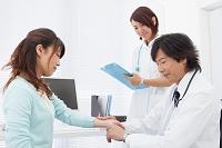 患者の脈を測る医師とカルテに記入する看護師