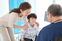 医師の診察を受ける男の子と母親