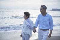 ビーチを散歩するシニアカップル