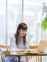 カフェでノートパソコンを見る日本人女性