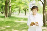 新緑と読書をするシニア日本人女性