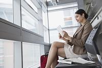 空港でタブレットを利用するビジネス女性