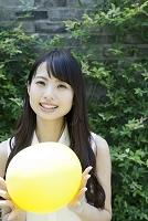 中庭で風船を持って立つ若い日本人女性