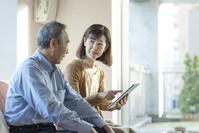 タブレットを操作する日本人シニア夫婦