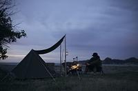 ソロキャンプで焚火にあたる日本人男性